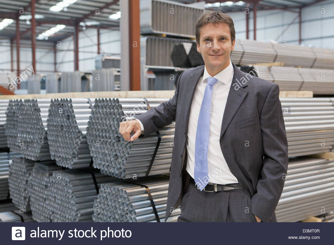 Portrait of confident businessman leaning on stacked steel bundles in warehouse - Stock Image