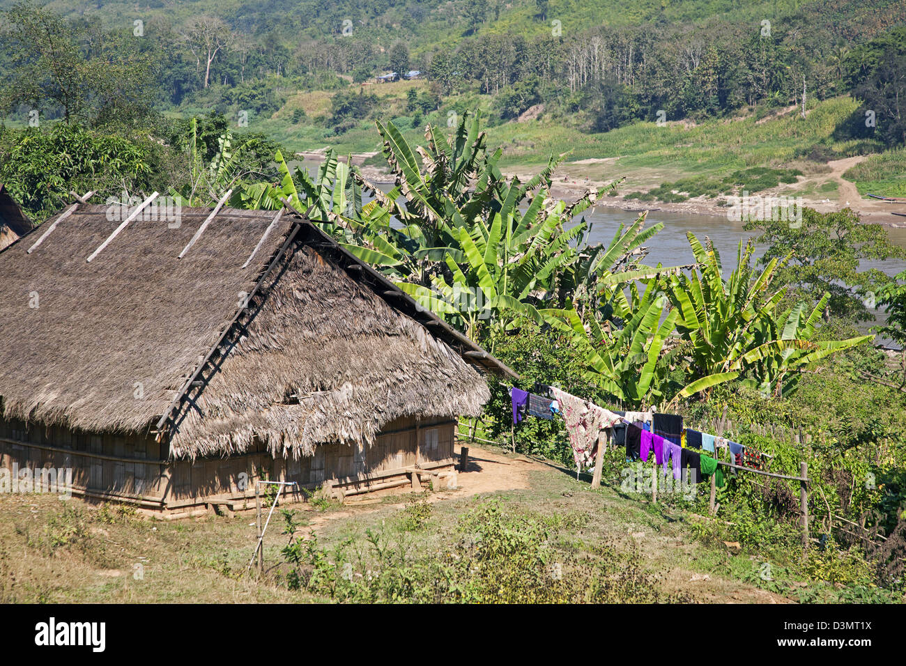 Traditional farmhouse with thatched roof and laundry drying on clothesline along the Mekong river, Laos, Southeast - Stock Image