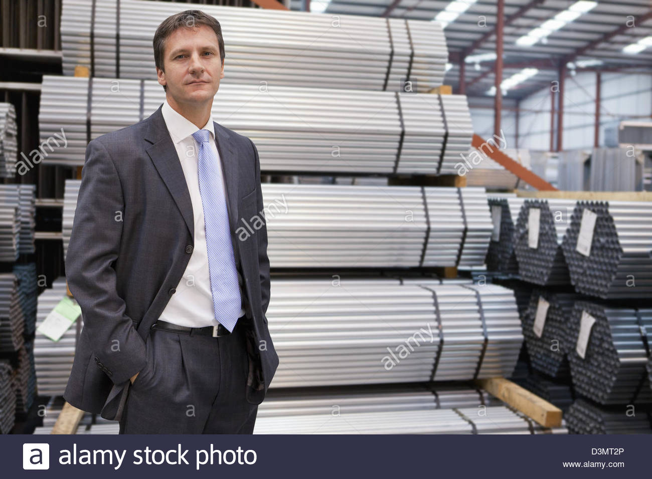 Portrait of confident businessman near stacked steel bundles in warehouse - Stock Image