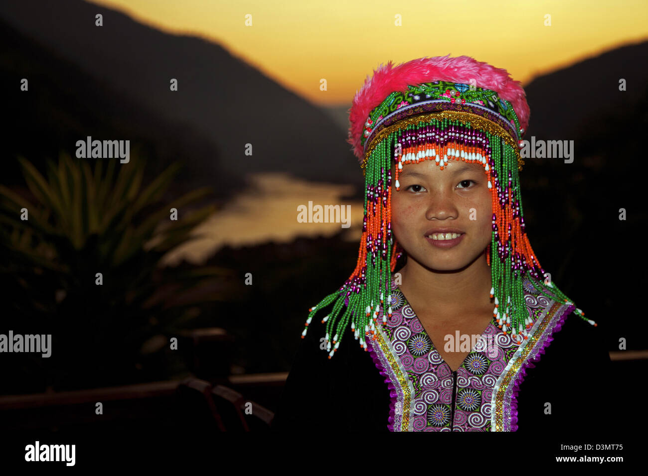 Traditional tribal dancer wearing headdress with colourful beads posing at sunset with view over the Mekong river, - Stock Image