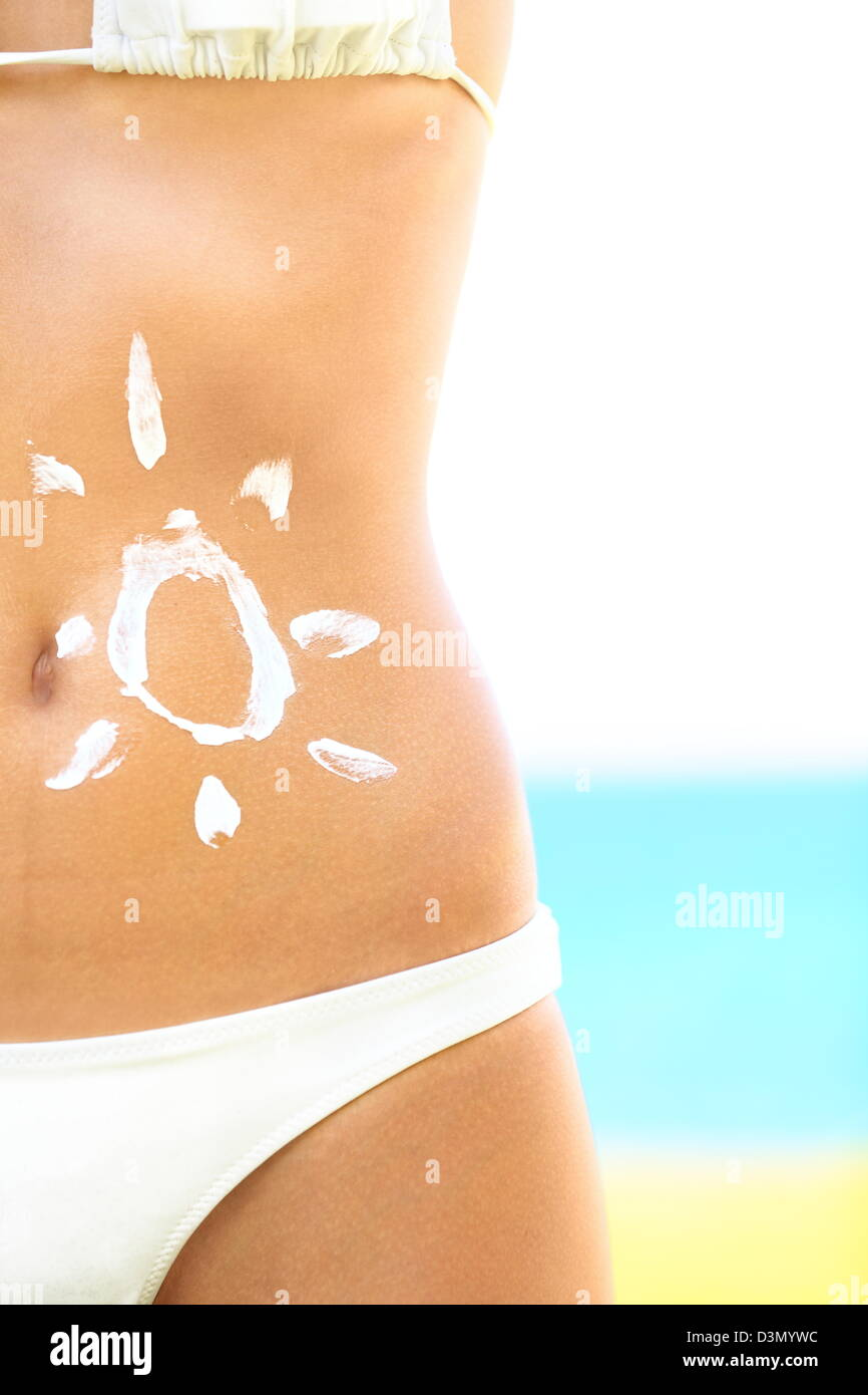 Sunscreen / sunblock woman. Solar cream protection drawing on suntan stomach of tan beautiful woman in bikini on - Stock Image