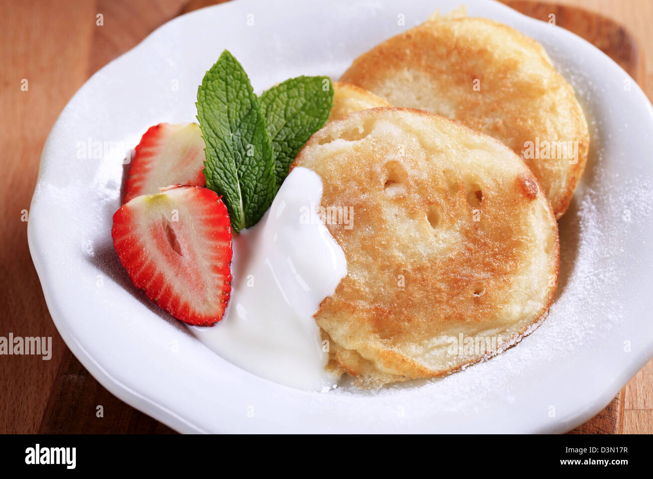 Small pancakes with sour cream and strawberry Stock Photo
