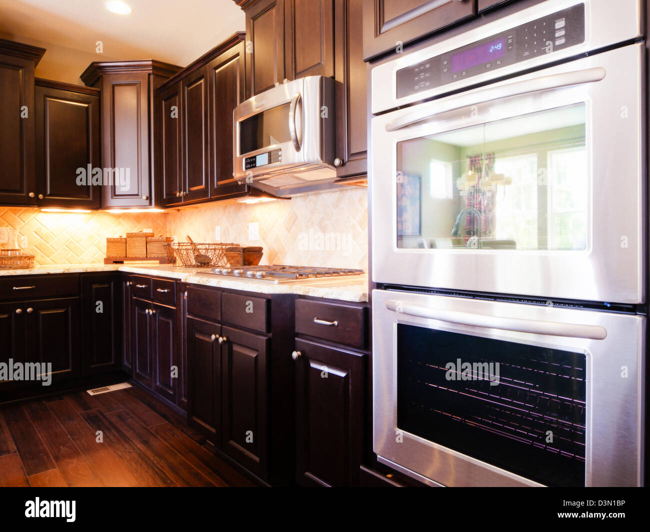 Modern kitchen with dark wood cabinets and hardwood floors Stock ...
