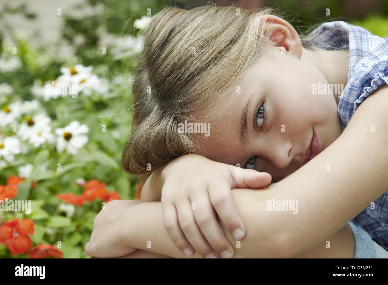7 year old girl hugging her knees - Stock Image