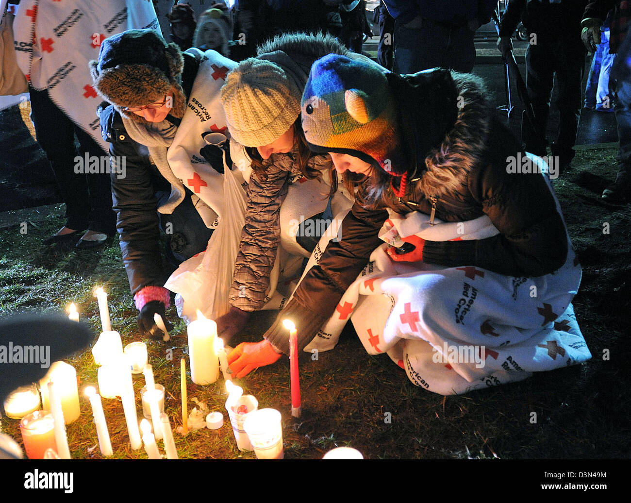 Mourners light candles during a vigil at Newtown High School following the Sandy Hook shooting spree in CT USA - Stock Image