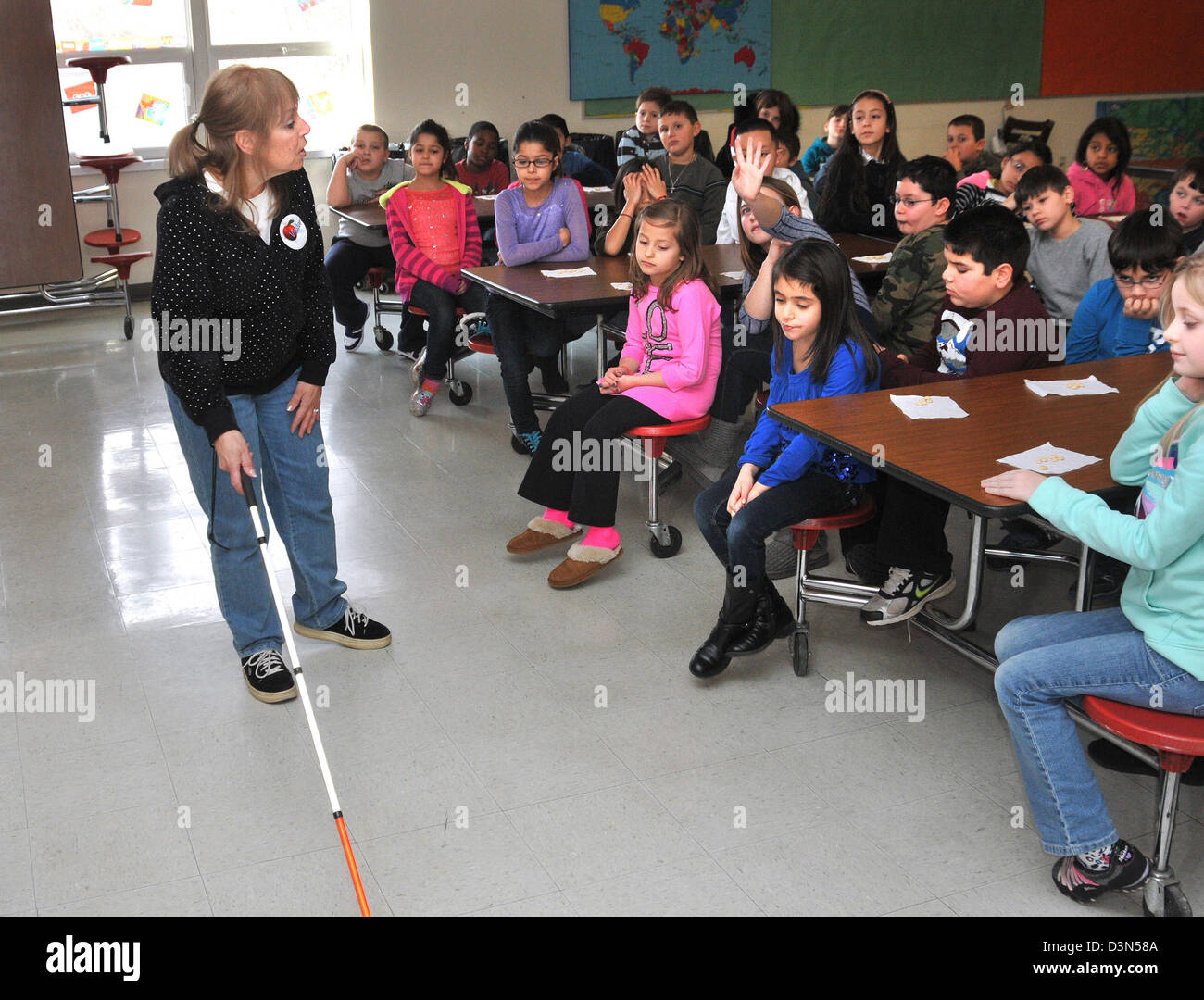 A teacher shows children how visually impaired people use a walking cane to help get around in a CT elementary school. - Stock Image