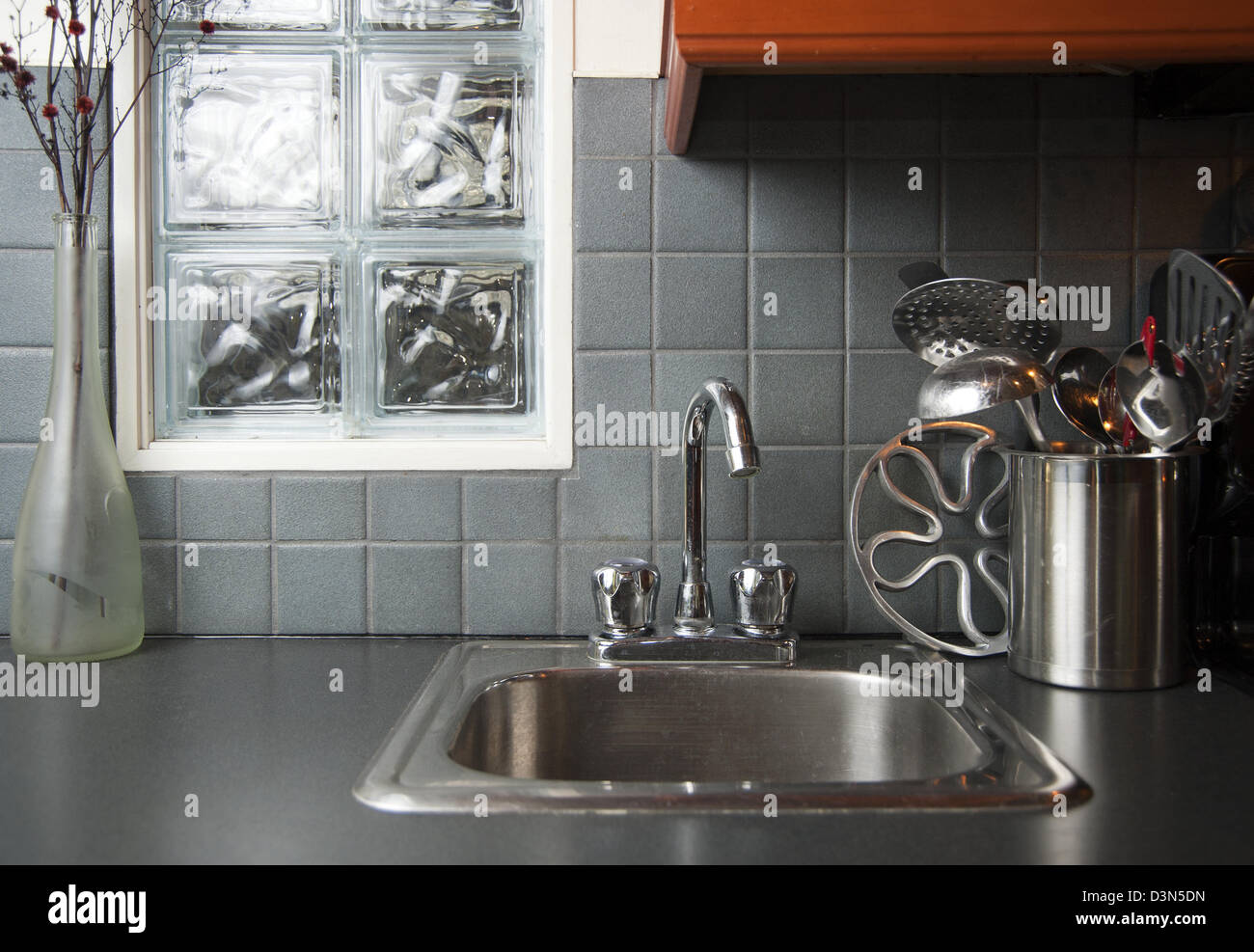 Kitchen sink and utensils on counter top beside sink - Stock Image