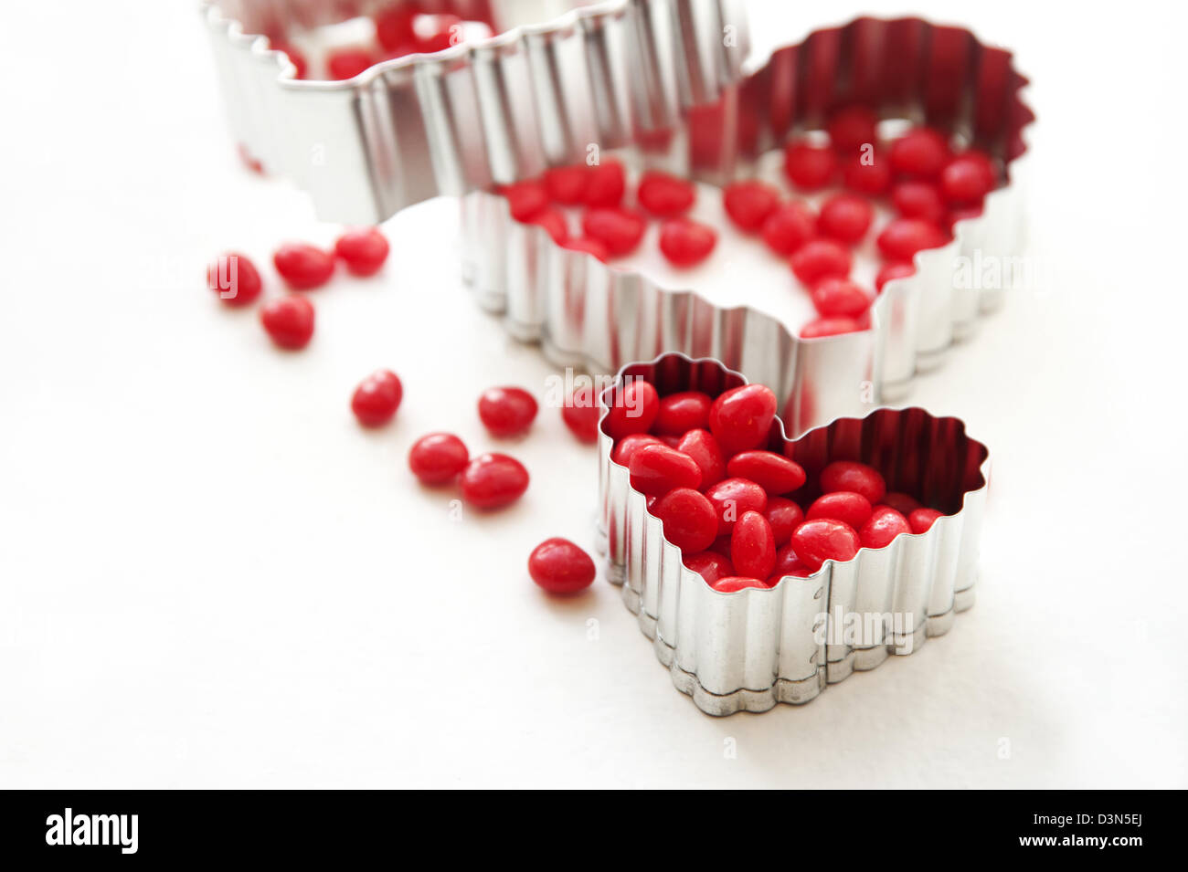 Red candy cinnamon hearts and heart shaped cookie cutters - Stock Image