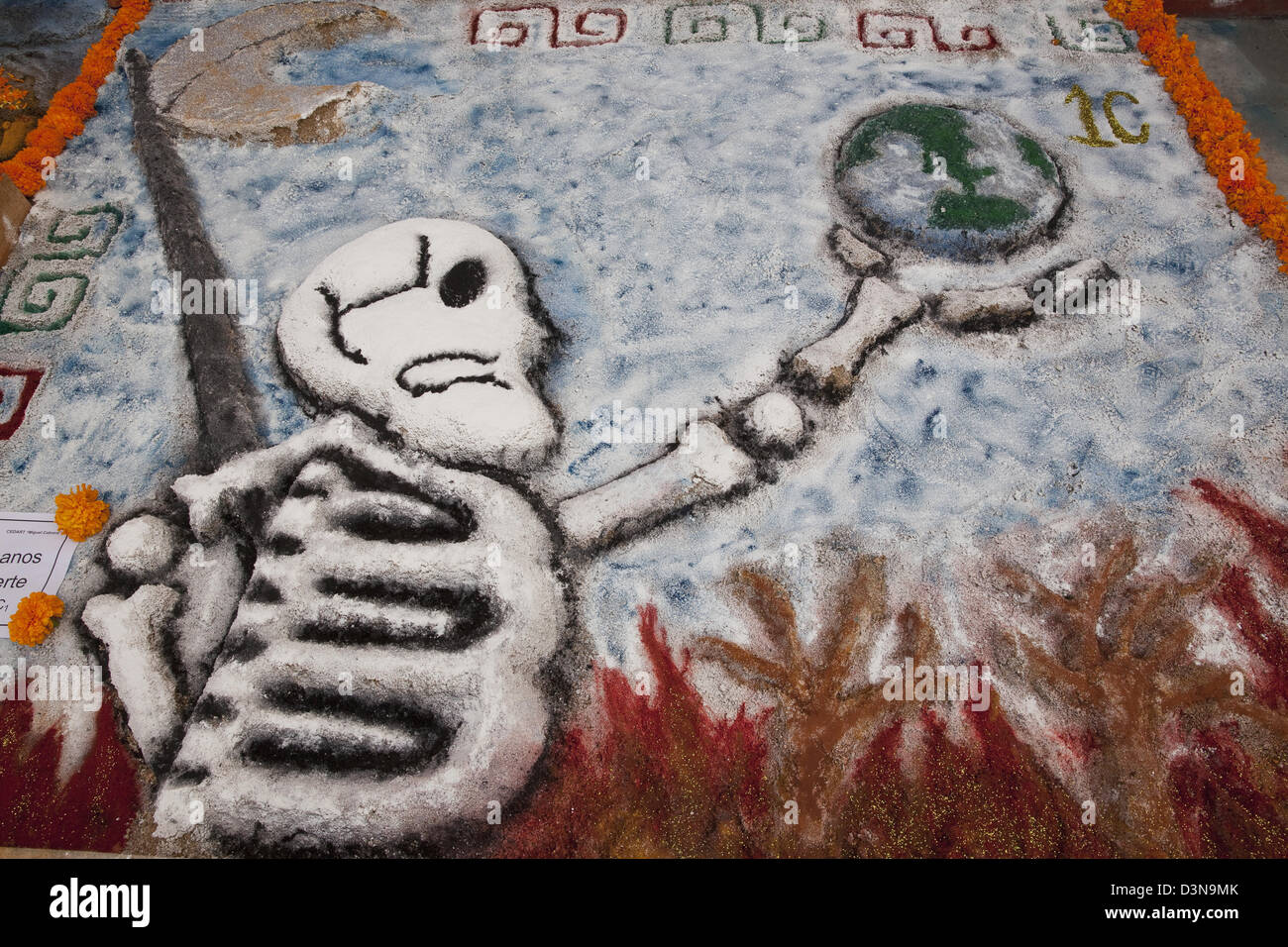 Sand painting of skeleton holding the heating earth created for Day of the Dead festival, Oaxaca, Mexico. - Stock Image