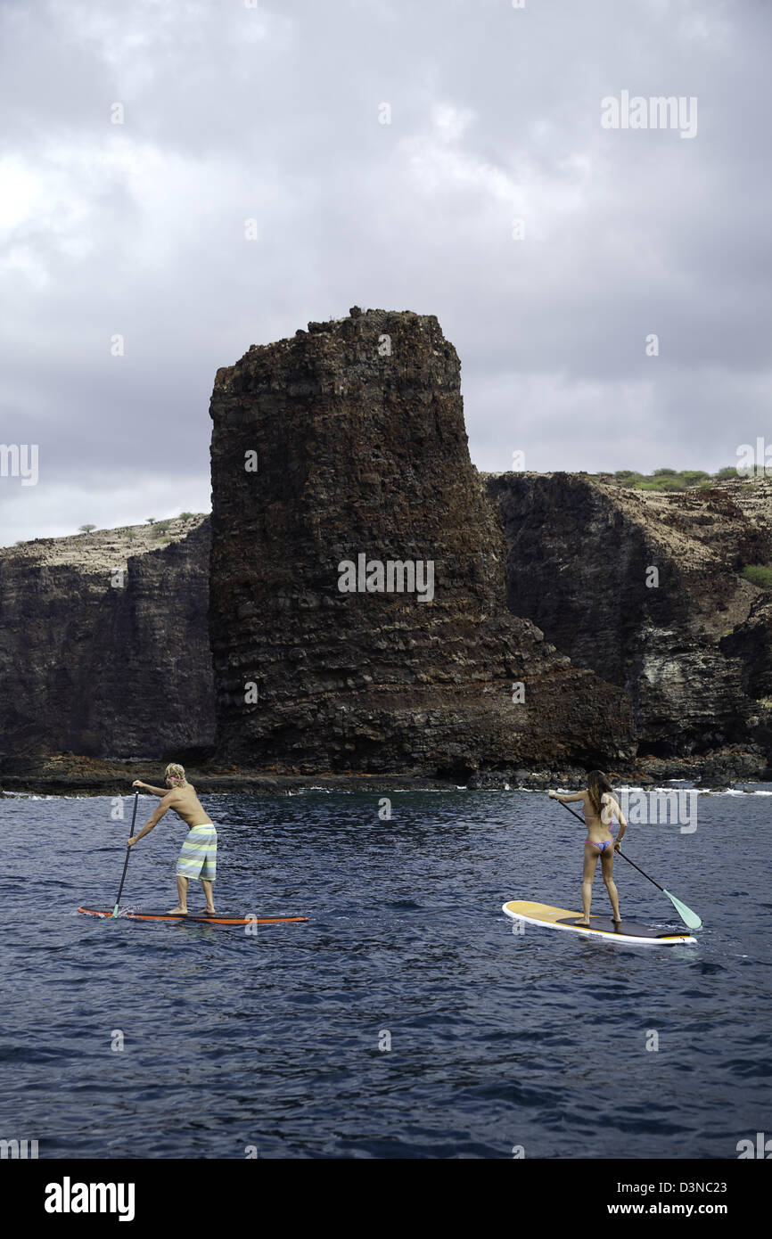 A young couple on stand-up paddle boards at Needles off the island of Lanai, Hawaii. Both are model released. - Stock Image