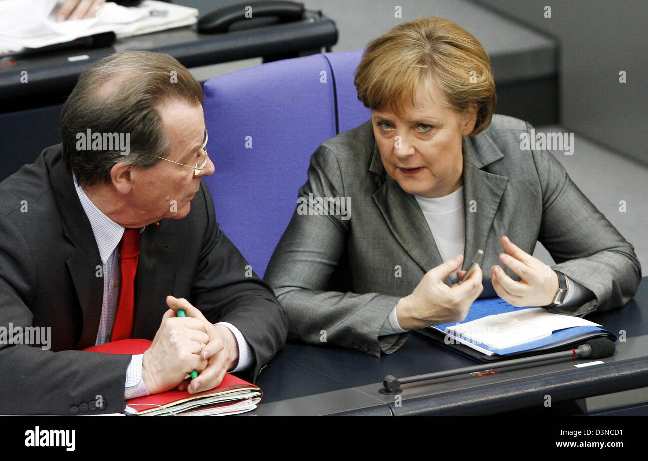 German Minister of Labour and Vice-Chancellor Franz Muentefering (L) and German Chancellor Angela Merkel (R) chat on the government bench in the Bundestag in Berlin, Germany, Tuesday, 28 March 2006. Four months after the start of the Grand Coalition the Bundestag budget debate begins today. The parliament will debate on the 2006 budget draft and the financial planning of the Federa Stock Photo