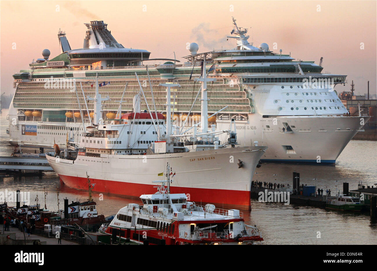 The giant cruiser 'Freedom of the Seas'  is watched by many onlookers while passing the museum ship 'Cap - Stock Image