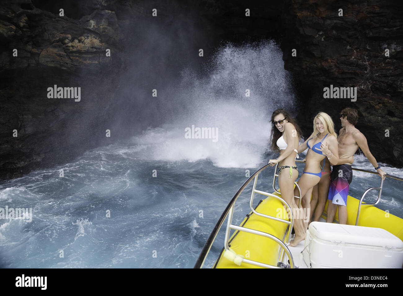 A group of young people (MR) on a hard bottom inflatable close to a large wave blowing out from a sea cave off Lanai, - Stock Image