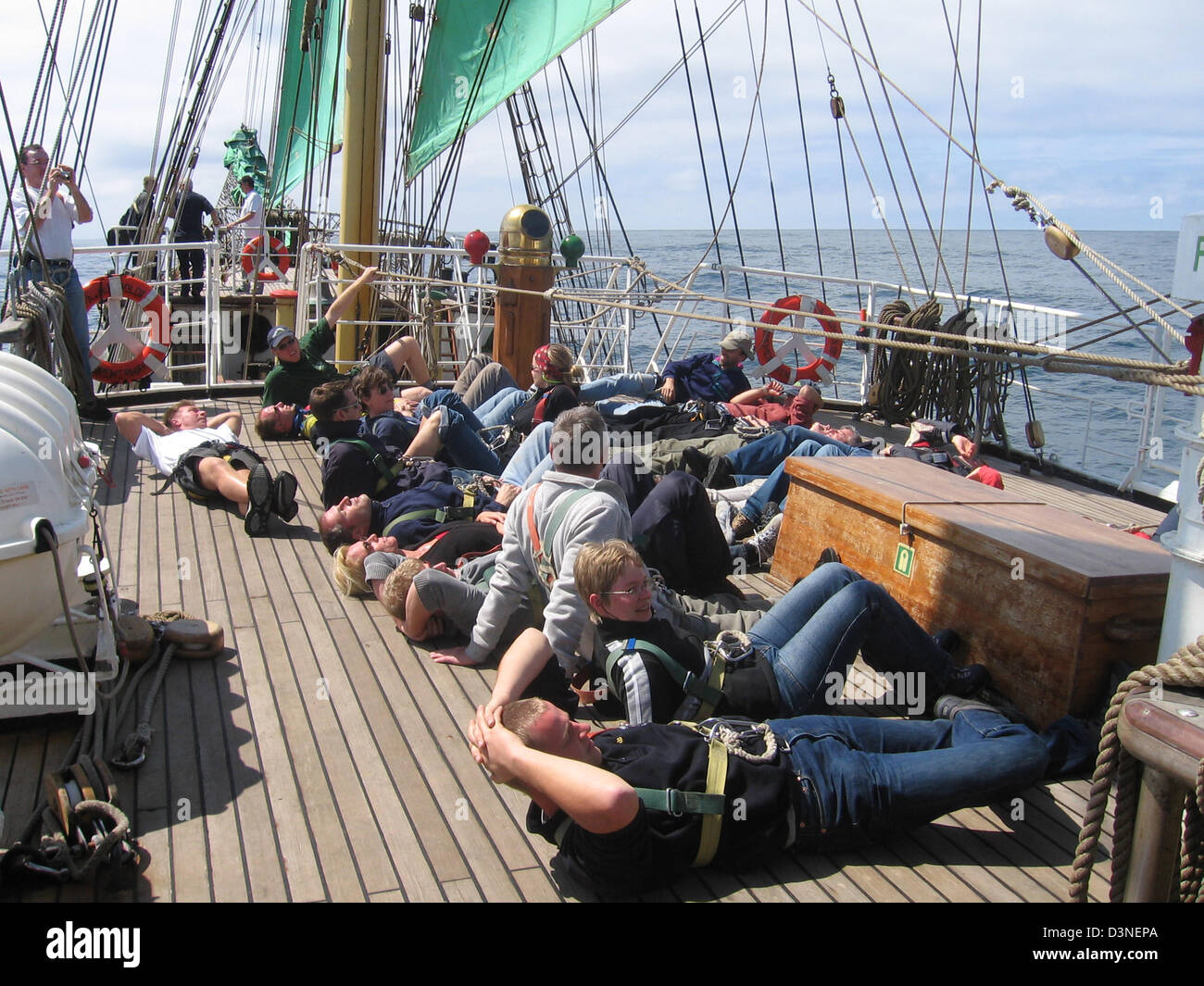 Tourists wait for the changing of the guards aboard the barque Alexander von Humboldt in the Pacific Ocean offshore - Stock Image