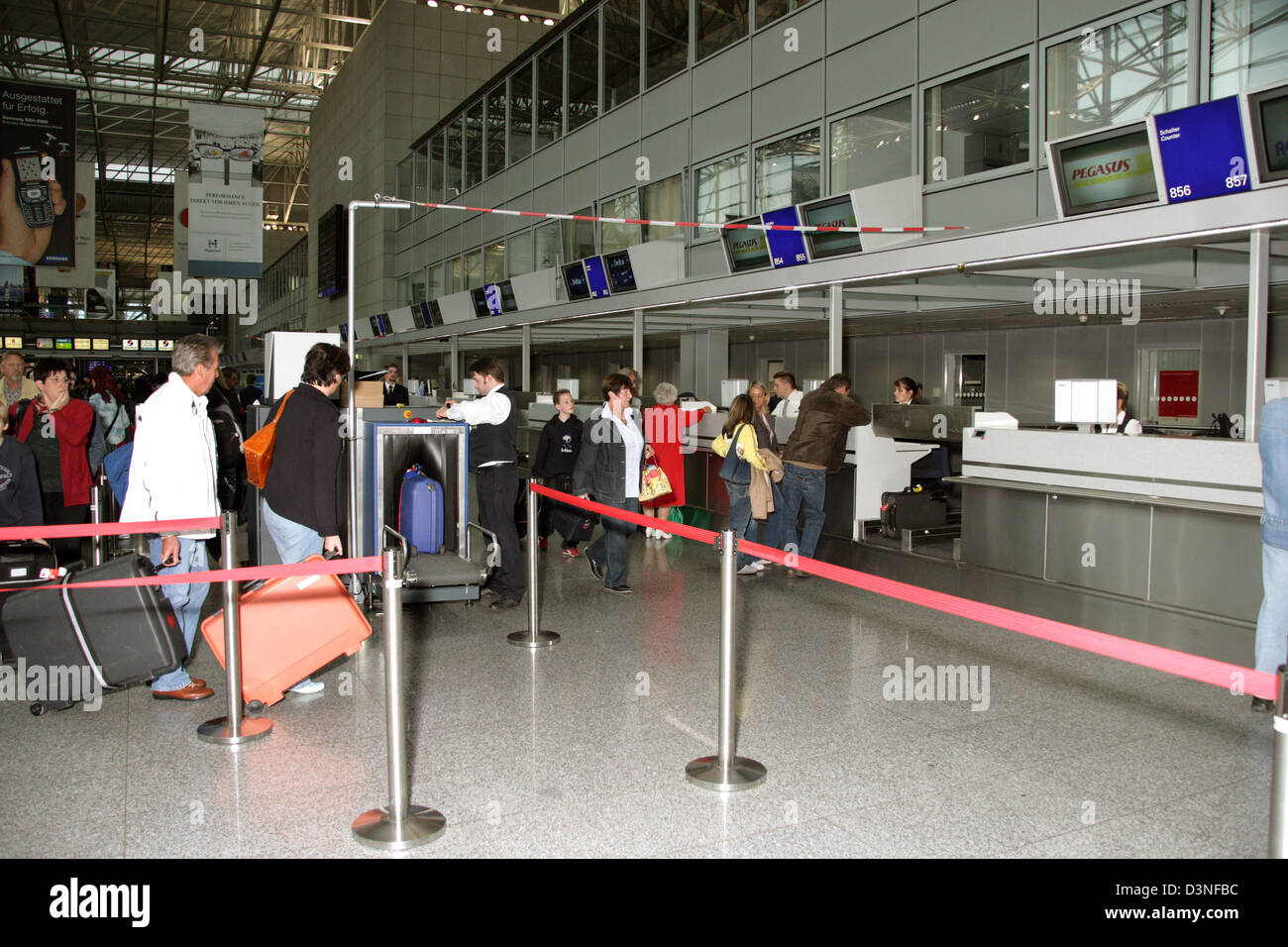 (dpa files) - Passengers have their luggage x-rayed prior to the check-in at the Terminal 2 of the Frankfurt Airport - Stock Image