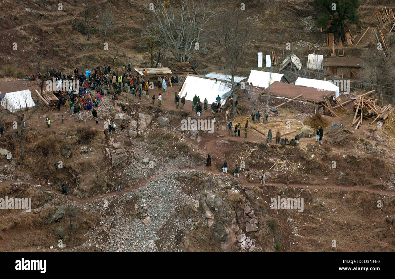 People assemble on a free space between destroyed buildings, one flight hour east of Muzaffarabad, Pakistan, 30 - Stock Image