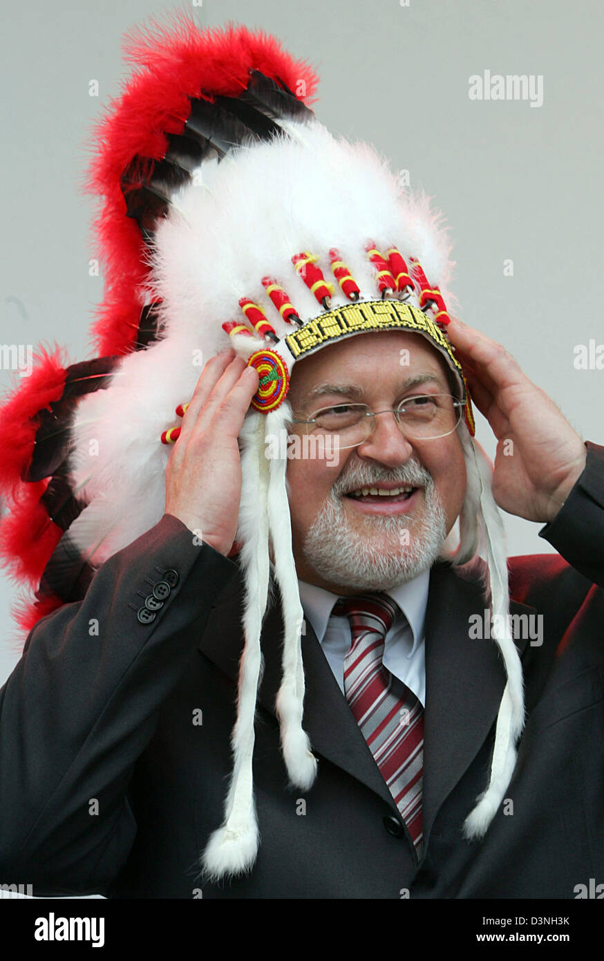 Peter Harry Cartensen, head of the German Council,  poses with a indigenous feathered headdress at German Council's - Stock Image