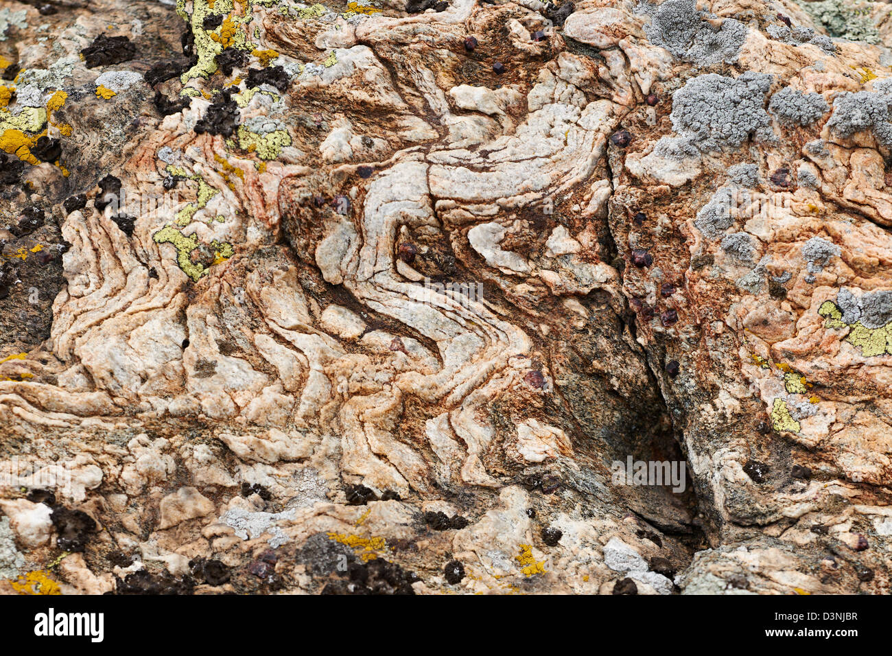 Magma rock with garnet crystals on land surface - Stock Image