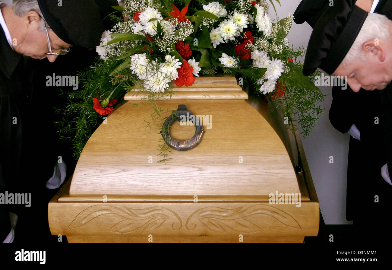 Pallbearers of funeral undertaker Karl Schumacher mark their respect to a deceased person in a mourning hall in - Stock Image