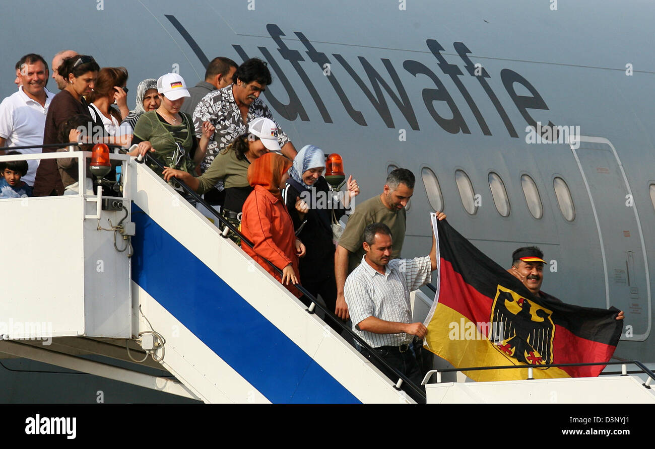 German refugees from the Lebanon wave a German flag as they get out of the Bundeswehr plane at the military part - Stock Image