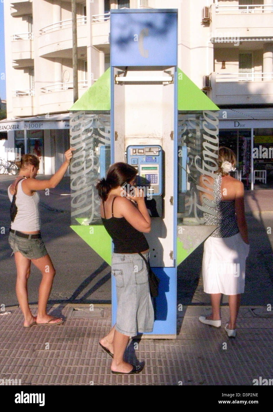 Women talk on public phones by telecommunication company telefonica in Cala Ratjada on Mallorca, Spain, Tuesday - Stock Image