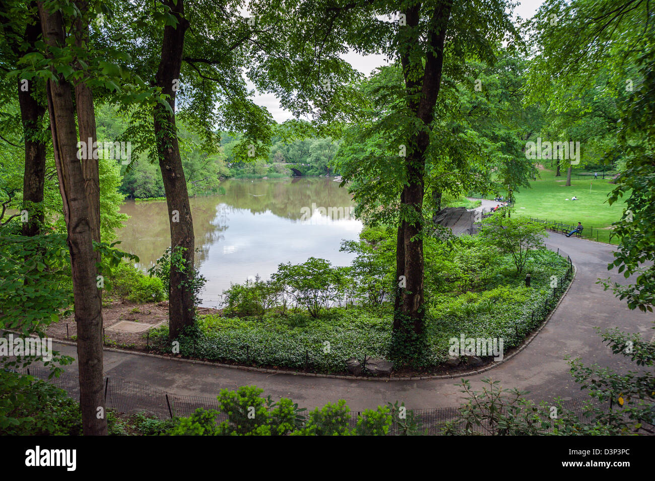 The beautiful, serene Central Park in NYC looking through the trees, across The Pond to the famous Gapstow Bridge. - Stock Image