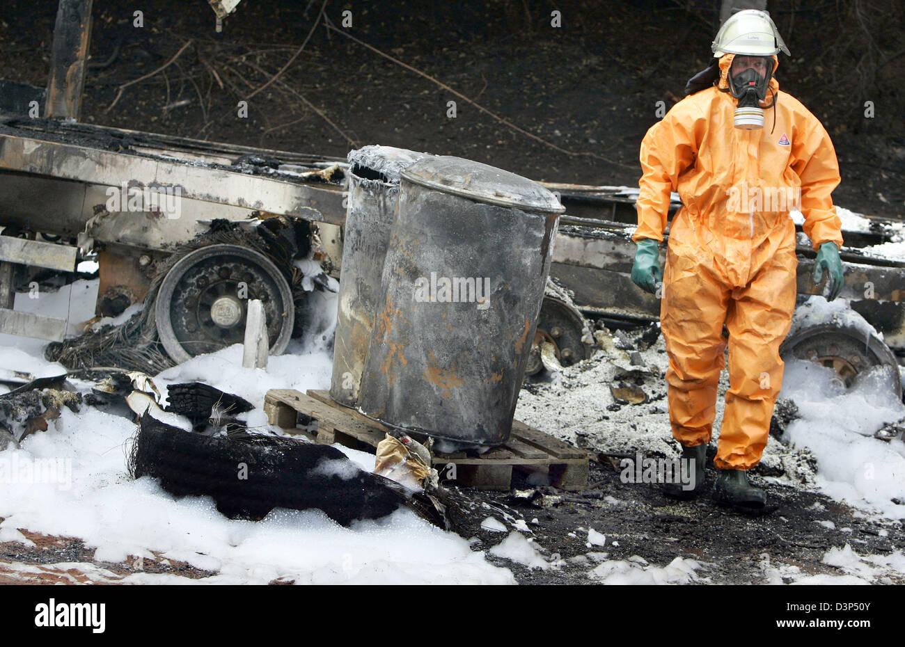 A fire fighter in protective clothing clears the scene of accident of the hazardous materials of an hazmat transportation - Stock Image