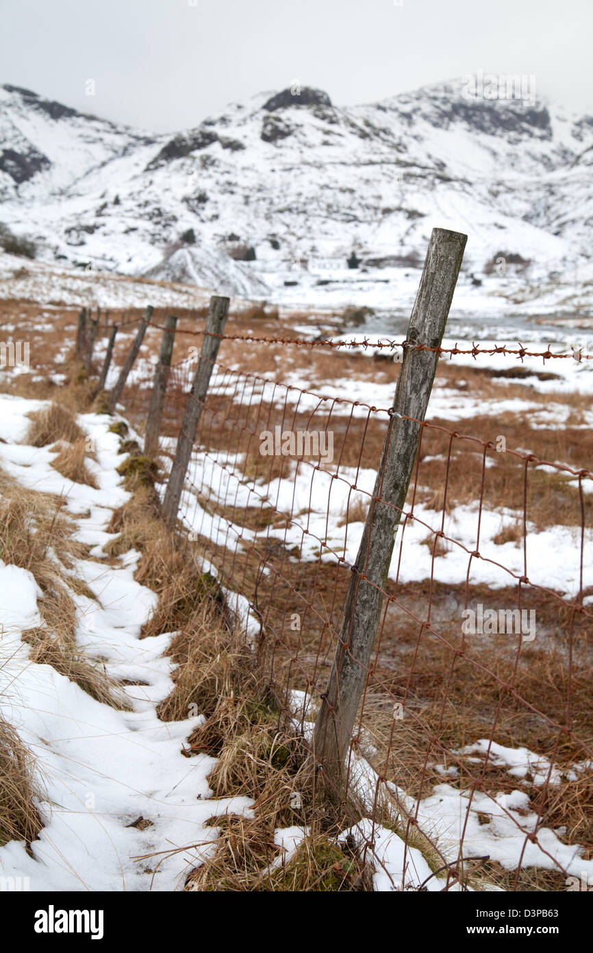 Old Barbed wire fence Coniston Copper Mines in winter with snow on the fells, Lake District, UK - Stock Image