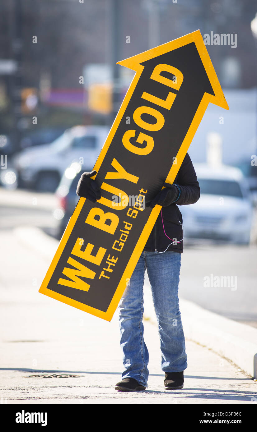 ARLINGTON, VIRGINIA, USA - Woman holds We Buy Gold sign on sidewalk to attract customers. - Stock Image