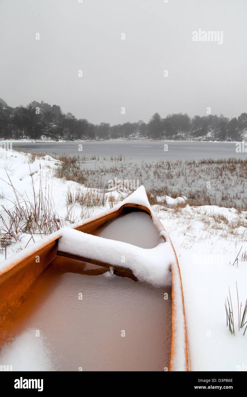 Orange canoe at Boretree Tarn, Finsthwaite Heights in heavy snow. - Stock Image