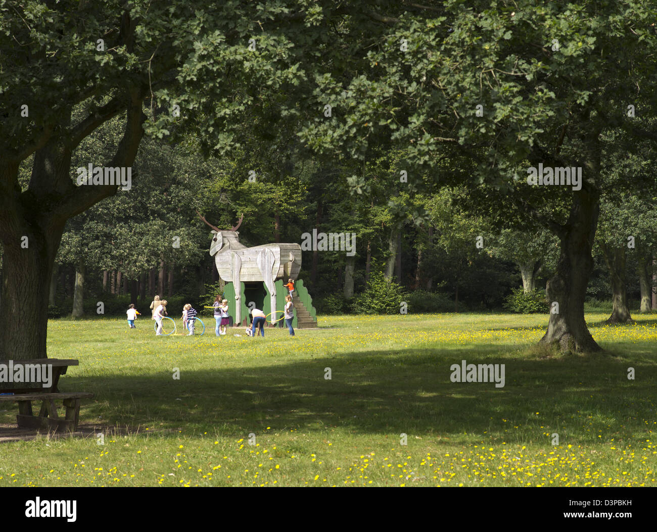 Children playing by wooden figure of a stag in Thetford Forest picnic site - Stock Image