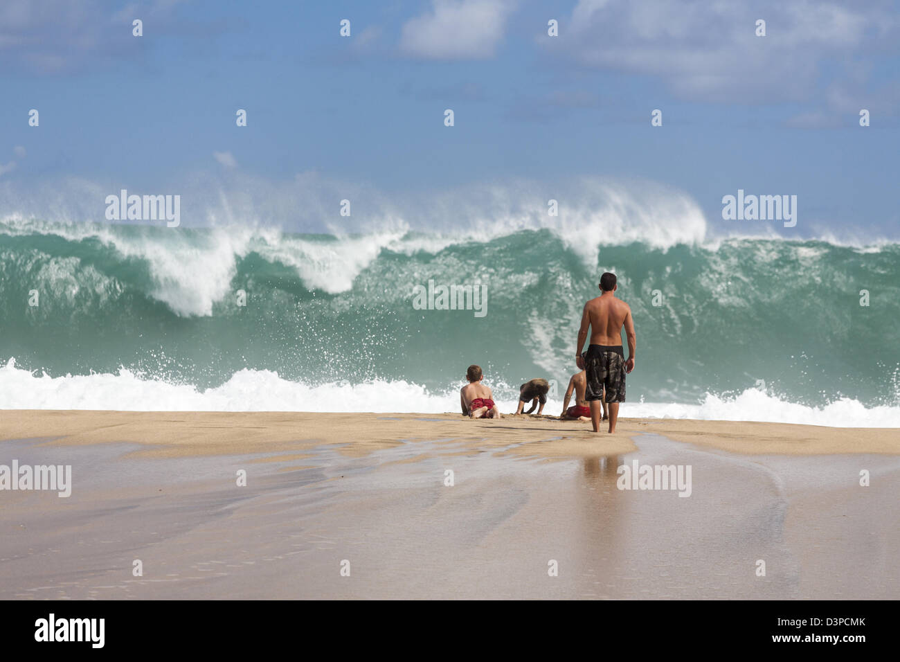 Here comes a really big one. A young family plays and watches the surf as a huge wave comes ashore on this north - Stock Image