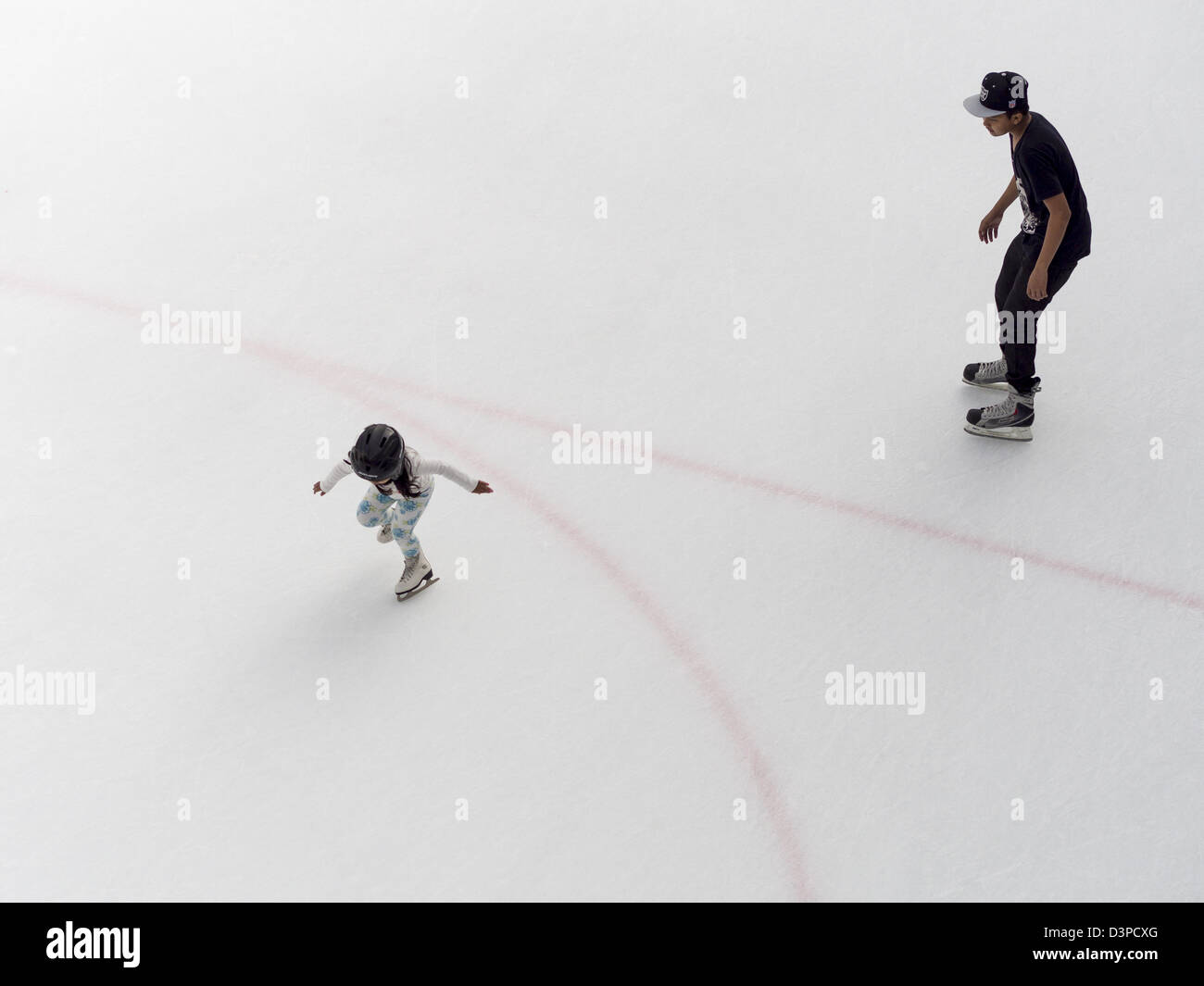 Learning to Skate. A young brother watches protectively or tentatively as his sister takes off on her skates. - Stock Image
