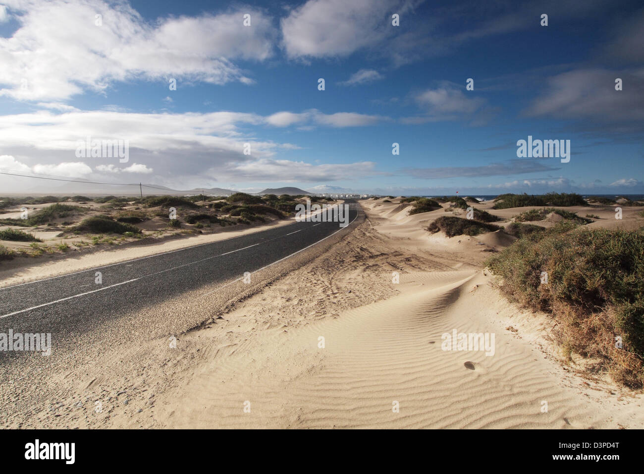 road through desert dunes near famara in lanzarote, canary islands, spain - Stock Image