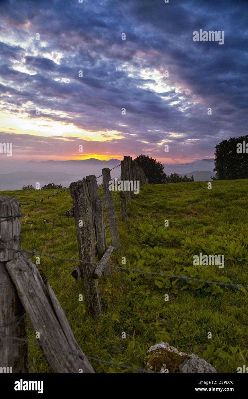 Sunrise in the Pyrenees shines light on the barbwire and wooden posts separate pasture land. Dramatic colored clouds - Stock Image