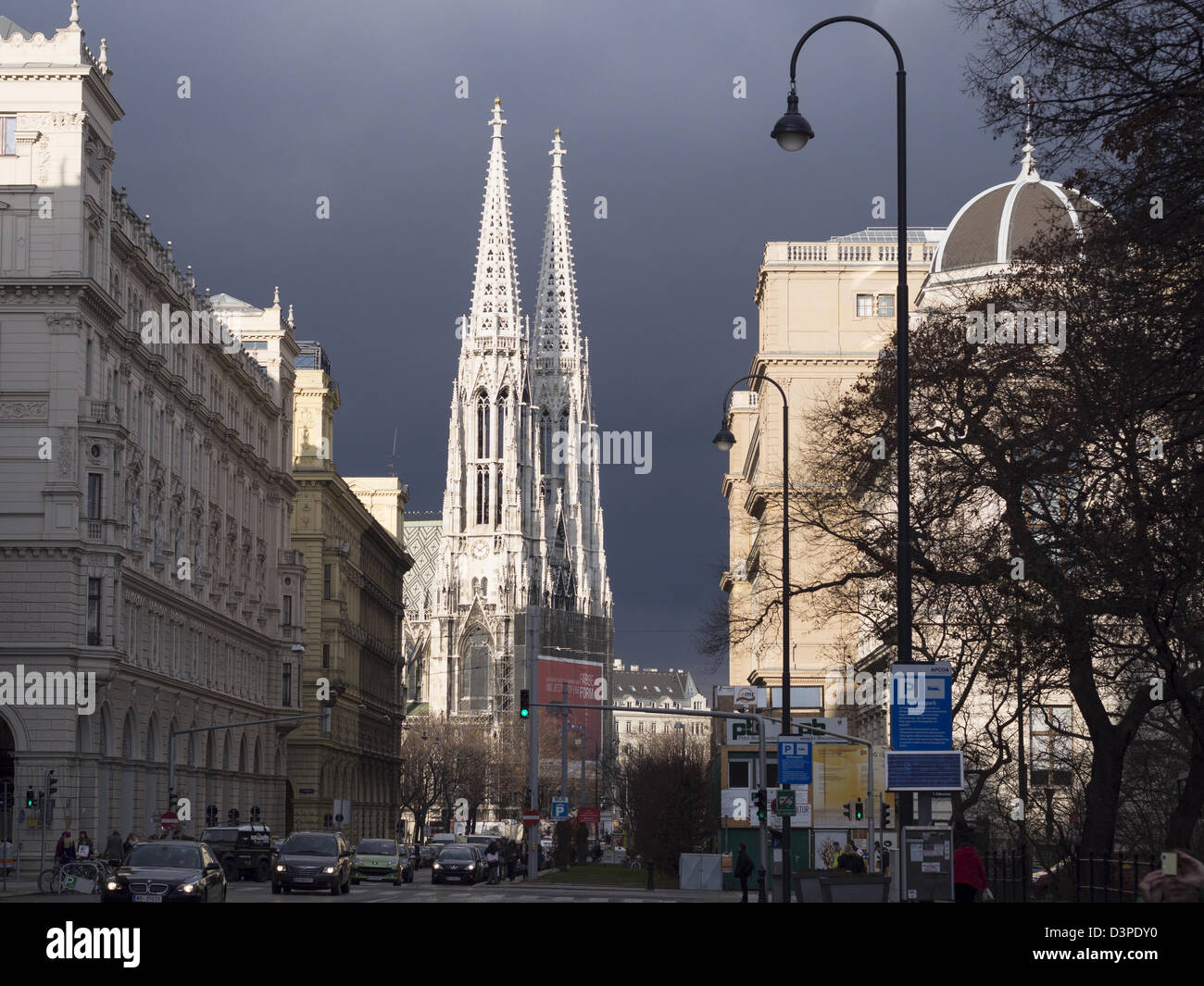 Votive Twin Towers and Ringstrasse. The bright stone of the filigreed towers of this landmark Vienna church highlighted - Stock Image