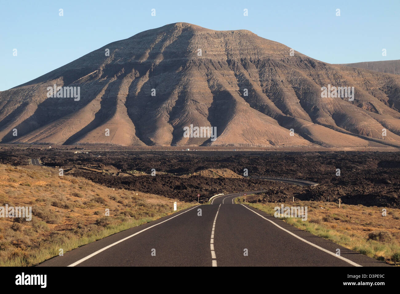 road through lava fields in timanfaya national park, lanzarote spain canary islands - Stock Image