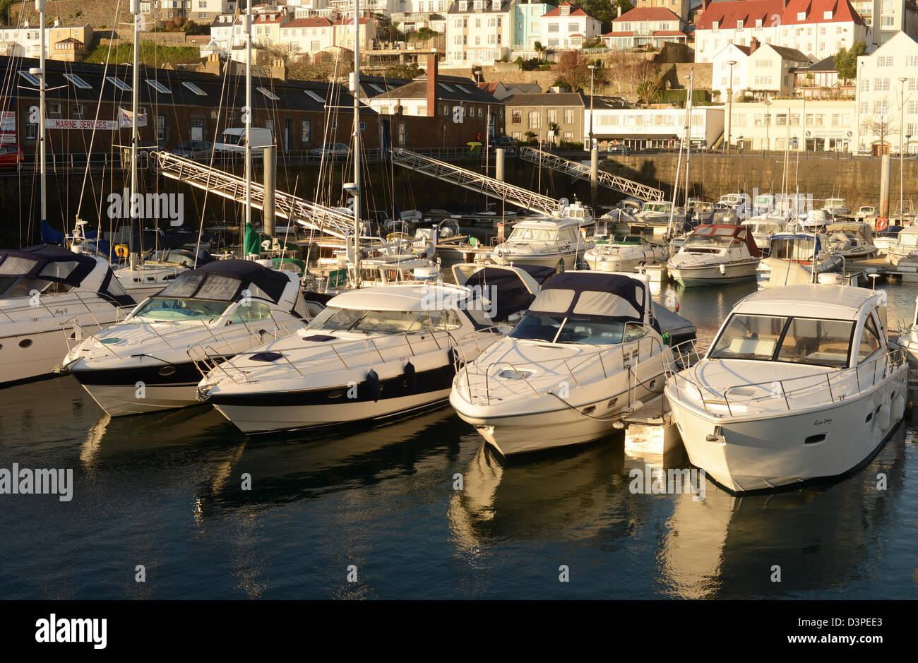 Motor cruisers moored in St Peter Port harbour, Guernsey at first light - Stock Image
