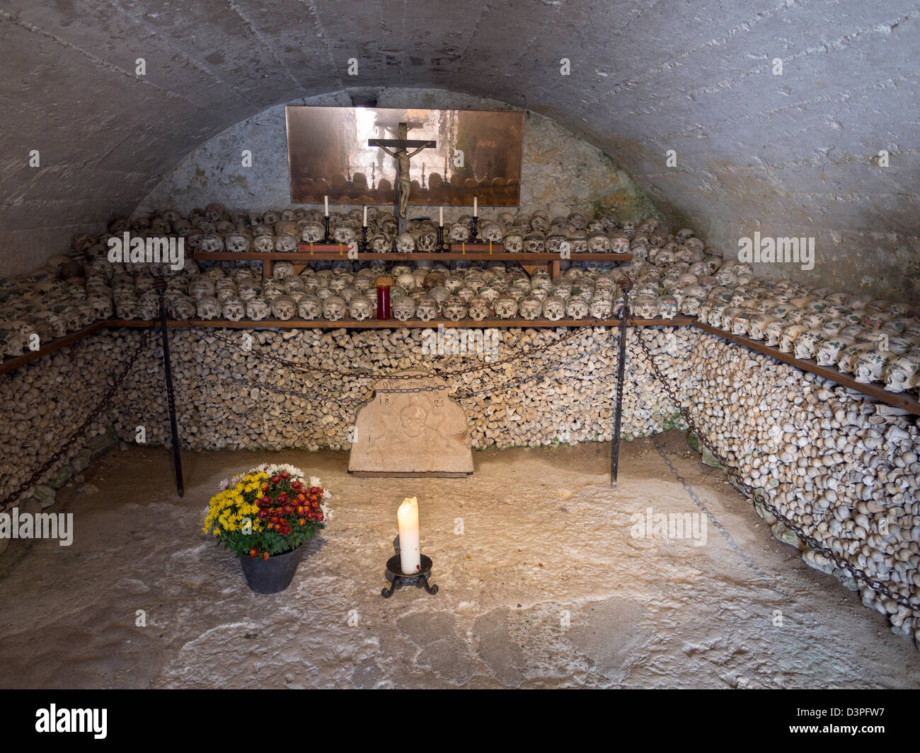 Hallstatt Village Ossuary. With decorated skulls above and long bones below the ossuary is a slightly unsettling - Stock Image