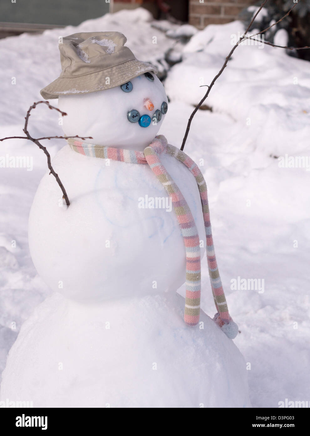 Well dressed snowman. A snowman with twig arms, a carrot nose, pastel scarf and bottle cap eyes. - Stock Image