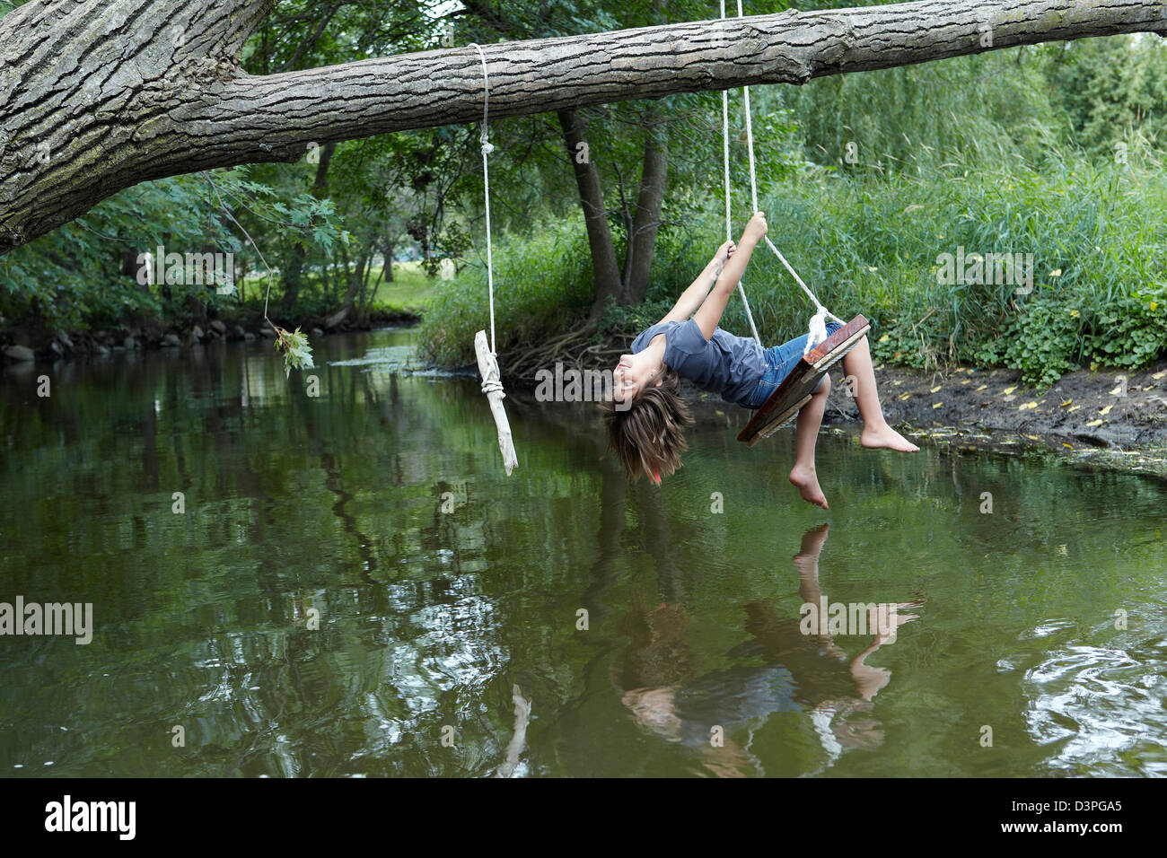 9 year old girl swinging above creek - Stock Image