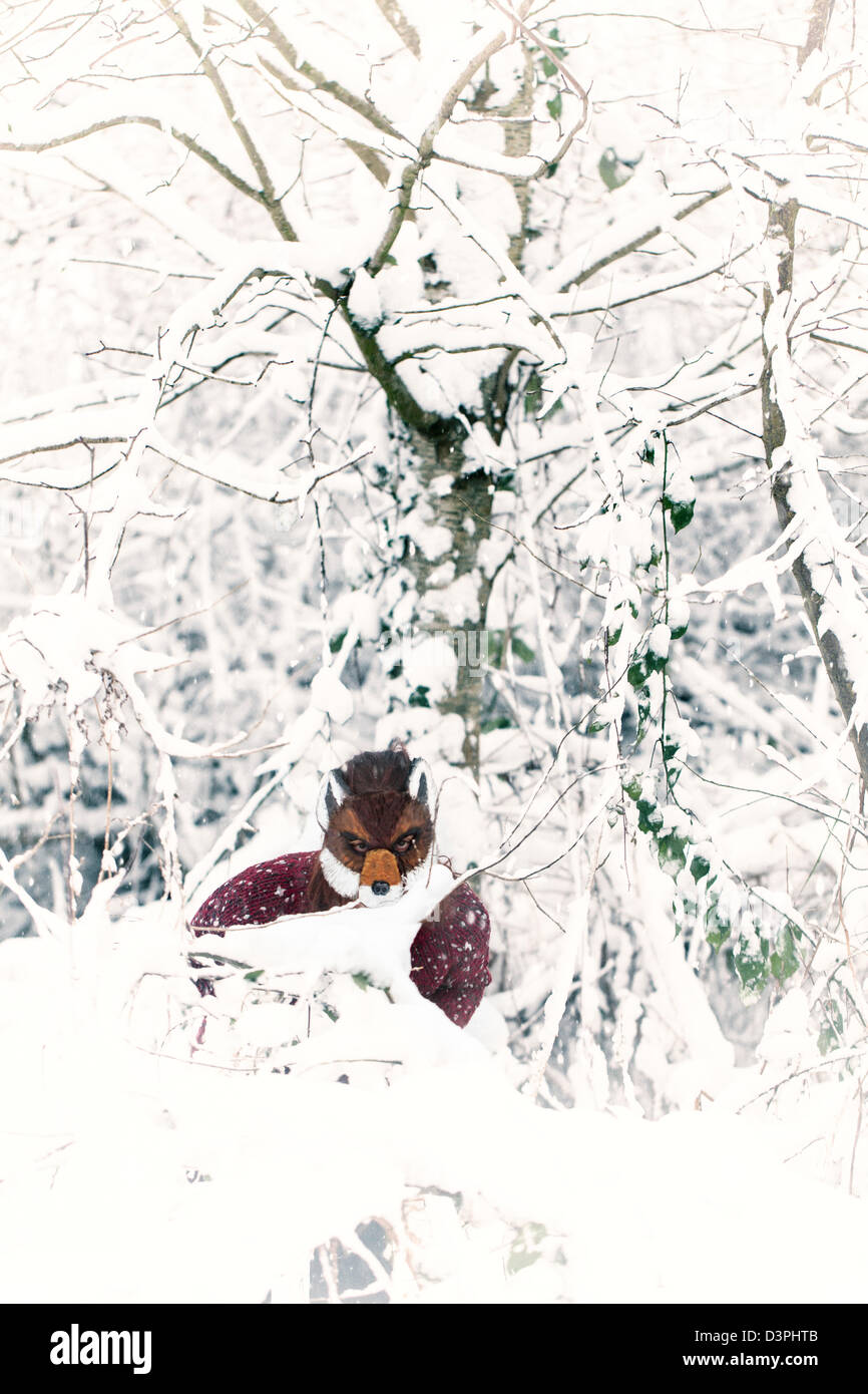 Woman wearing a fox masking in the snow - Stock Image