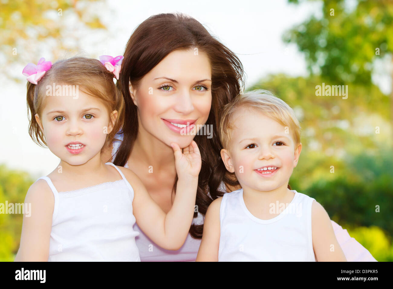 Photo of beautiful woman with two cute kids, closeup portrait of young mother with sweet daughter and lovely son Stock Photo