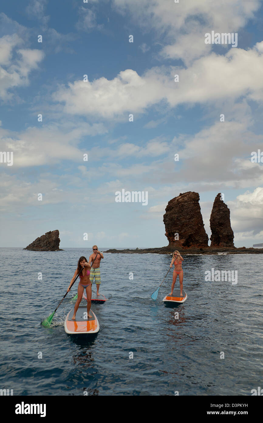Three young people on stand-up paddle boards at Needles off the island of Lanai, Hawaii. All three are model released. - Stock Image