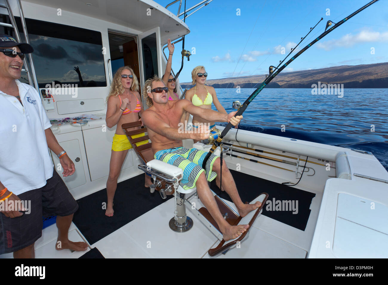 The crew and clients on a sportfishing charter boat off the island of Lanai, reeling in a fish, Hawaii. - Stock Image