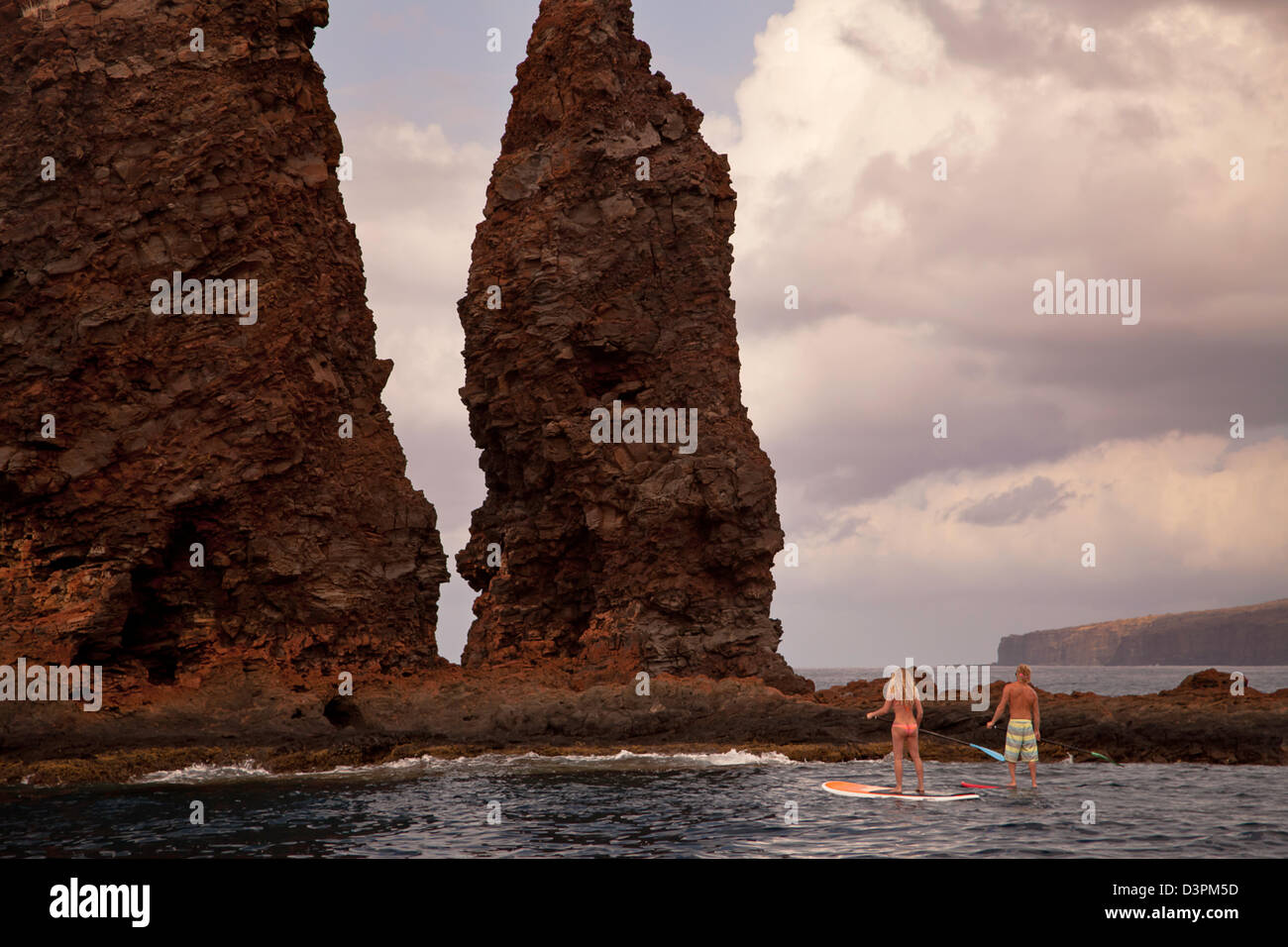 A couple on stand-up paddle boards at Needles off the island of Lanai, Hawaii. Both are model released. - Stock Image