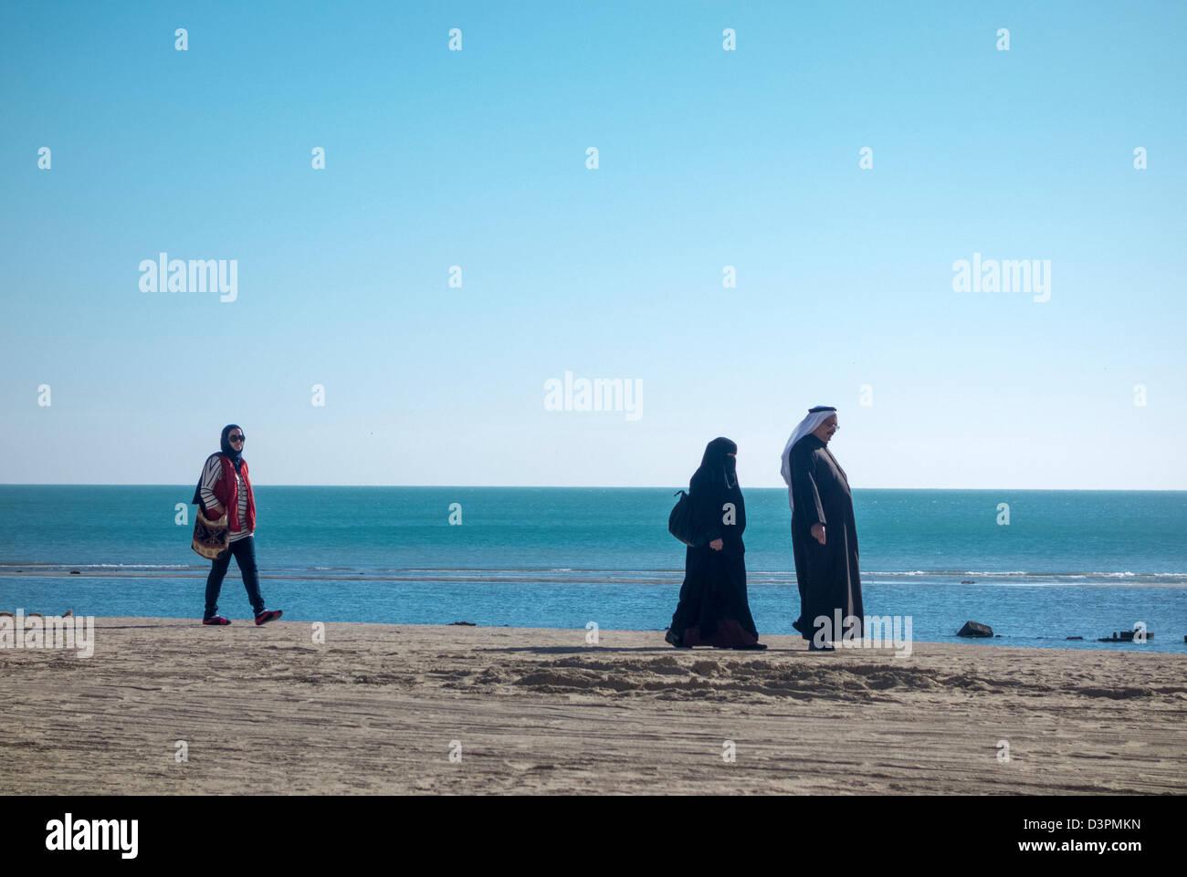 Arab family walking on beach, beside Mövenpick Hotel & Resort, Al Bida'a, Kuwait Stock Photo