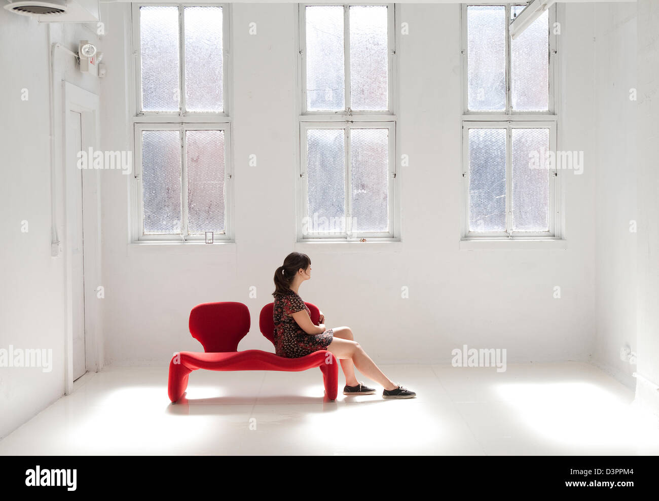 GIrl sitting in a blank room with a red sofa - Stock Image