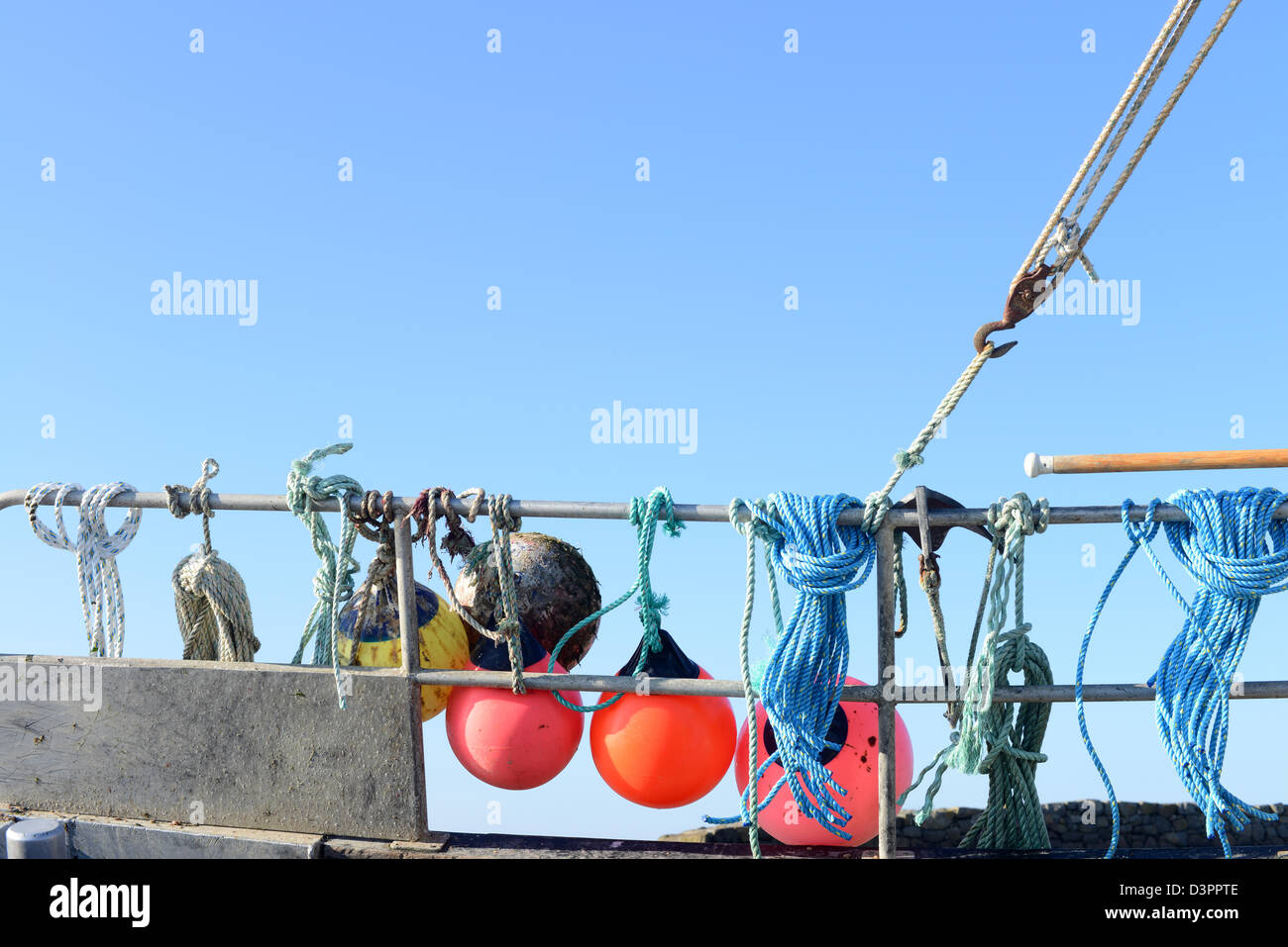 Fishing marker bouys on the hand rails of a fishing trawler in Guernsey - Stock Image