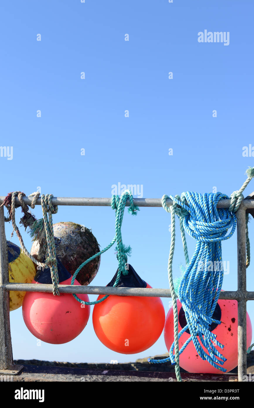 Fishing marker buoys on the hand rails of a fishing trawler in Guernsey - Stock Image